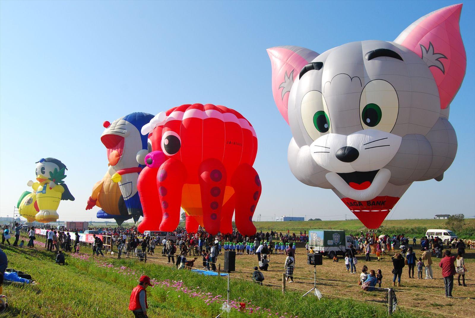 各种可爱动物,卡通造型的热气球在河岸旁一字排开,远看俏皮无比,但近